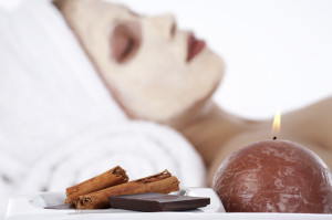 Girl witn facial mask with cinnamon and chocolate in front (focus on cinnamon and chocolate)